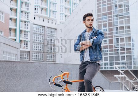 Man riding a bicycle outside. Serious man with crossed hands looking near. He made a stop on his orange bike. Urban background