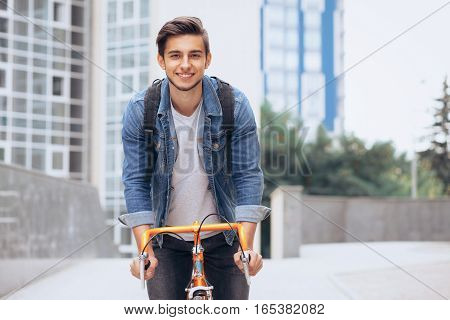 Man riding a bicycle outside. Handsome boy is glad to have some fun during the summer leisure time. Happy guy looking at camera. Urban background