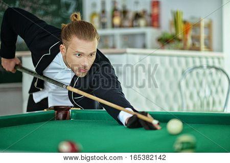 Young handsome man playing billiard in billiard club
