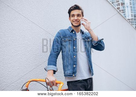 Cheerful young man talking on the mobile phone and smiling while standing near his bicycle. Wall background. Close up