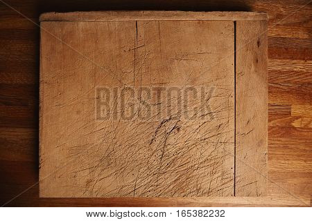 Side of a very old and heavily used chopping board with deep cuts on a beautiful brown wooden table