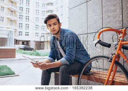 Young man using the tablet sitting on the bench. Handsome guy looking at camera with nice smile on his face. Urban background