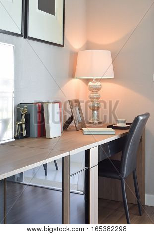 Wooden Table With Lamp And Books In Modern Working Room Interior