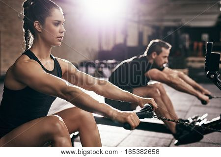 People In Gym Execising On Weigh-lifting Machine