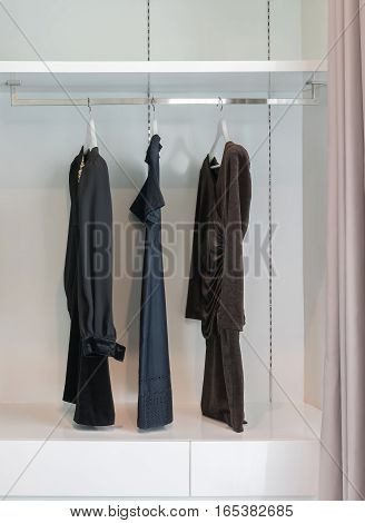 modern closet with row of black dress hanging on coat hanger in wardrobe.