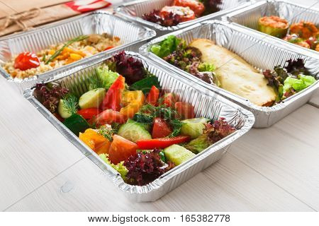 Healthy eating, diet concept. Take away organic food. Weight loss nutrition in foil boxes. Vegetable salad on white wood