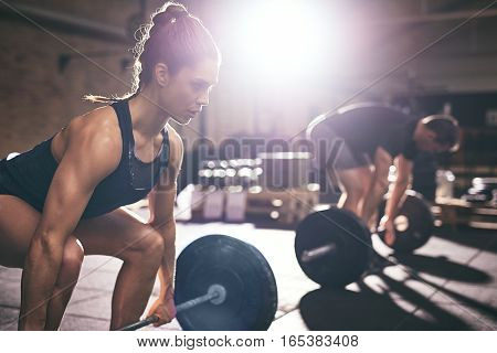 Muscular Man And Woman Lifting Heavy Barbells