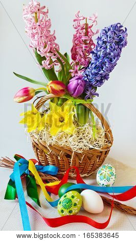 Traditional Czech easter decoration - whip with ribbons with hyacinth tulips and daffodisl and decorated eggs