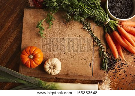 Black beluga lentils in a bowl, bunch of carrots, rosemary, leeks and miniature pumpkins lying around an old chopping board with deep cuts