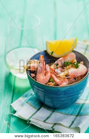 Shrimps in blue bowl with lemon and wine, copy space