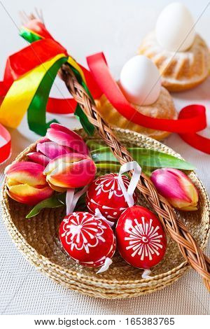Traditional Czech easter decoration - regional whip with ribbons with tulip and decorated red eggs in the wicker scuttle. Spring easter holiday arrangement.