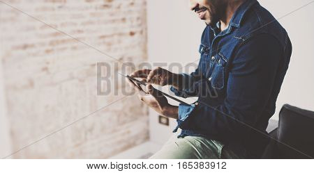 Attractive bearded African man using tablet at his empty room.Concept of young people enjoying mobile devices.Blurred brick wall on the background.Color filter.Wide