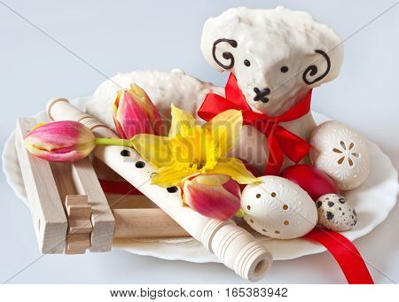Traditional Czech easter decoration - white lamb cake with tulips and daffodil lacy white eggs flute and regional ratchet. Spring easter holiday arrangement.