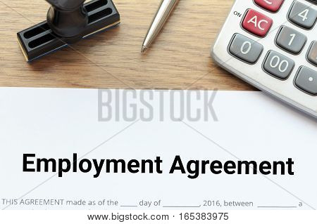 Top view of Employment agreement lay down on wooden desk with rubber stamp and calculator.