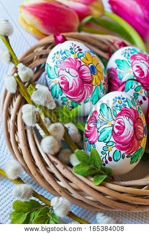 Traditional Czech easter decoration - colorful painted eggs in wicker nest with pussycats and tulips