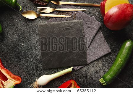 Peppers, leeks, zucchini and mango with golden utensils lying around an empty black slate board on black background, top view presentation with space for your text in center