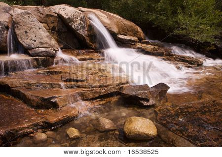 Small single waterfall cascading down mountain boulders into shallow water