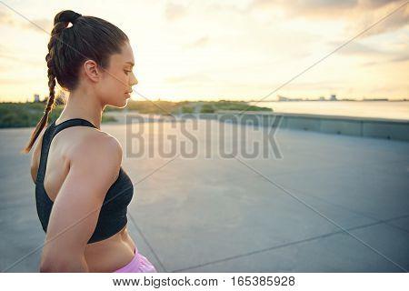 Side View Of Calm Sportswoman Near Waterfront