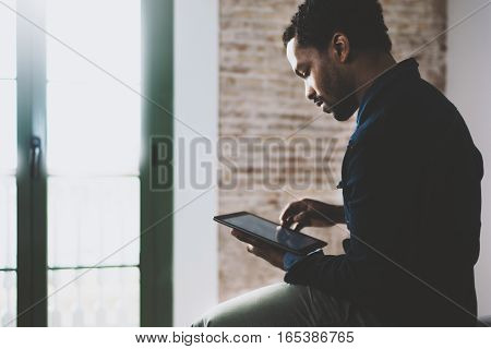 Closeup of young bearded African man using laptop while sitting on sofa at his modern home office.Concept of people working with mobile gadget.Color filter.Blurred window and brick wall the background