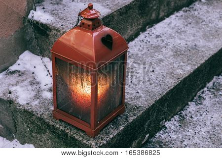 Decorative lantern with candle at outdoor snowy stair selective focus