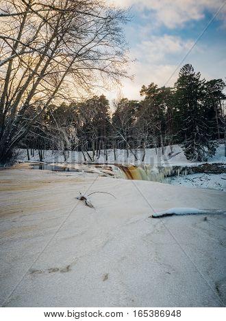 Partly frozen Keila-Joa waterfall by winter sunset. Long exposure vertorama. Harjumaa Estonia