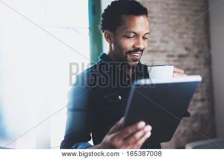 Closeup of young bearded African man using tablet while holding white cup of coffee in hand at modern coworking office.Concept people working with mobile gadget.Blurred brick wall on the background