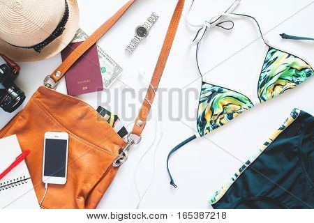 Flat lay set of summer items. Girl items with bikini watch mobile phone camera and passport for summer vacation on white background