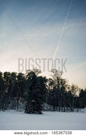 Airplane track on sunset sky winter scene on foreground vertical composition