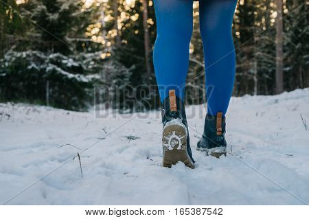Female legs in trendy boots and blue tights against snowy forest. From ground back view