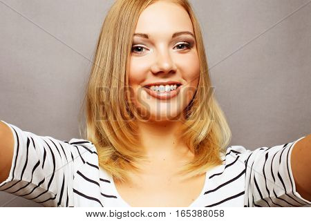 Selfie time. Joyful young women making selfie by her smart phone over grey background
