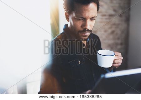 Closeup view of young bearded African man using tablet while holding white ceramic cup in hand at modern coworking office.Concept people working with mobile gadget.Blurred background, flare effect