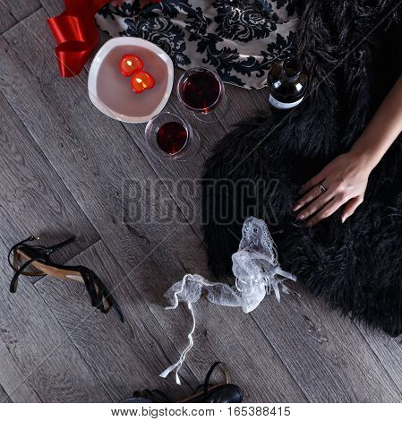 Two wine glasses heart shaped candles lingerie scattered in a party aftermath on silk and fur on floor female hand rest on fur top view
