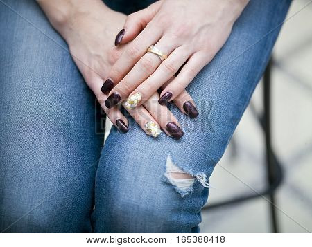 Female manicured hands, crossed, laid on the knees wearing ripped jeans. Selective focus closeup