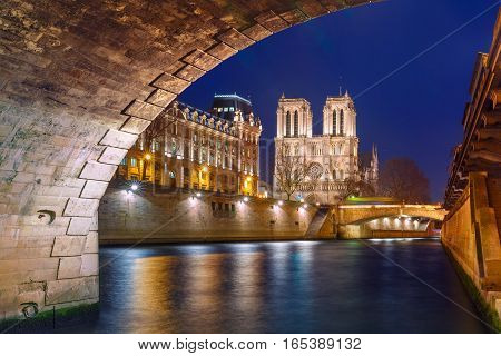 Cathedral of Notre Dame, Petit Pont and riverside of Seine river in Paris at night, France