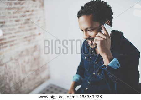 Closeup of young bearded African man making conversation on smartphone at modern home office.Concept people using mobile devices.Blurred wall background