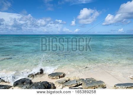 Small wave hitting stones on Grand Turk island beach (Turks & Caicos).