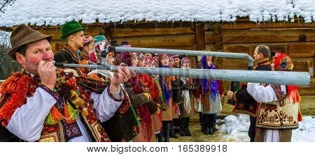Uzhgorod Ukraine - January 15 2017: Member of folklore band plays on trembita during the seventh ethnic festival Christmas Carols in the old village. During the festival visitors can familiarize with a variety of Christmas customs caroling and celebration