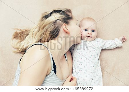 mother kissing her infant baby girl in the bed