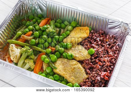 Healthy food restaurant delivery and diet concept. Take away of fitness meal. Weight loss lunch in foil boxes. Meat with brown rice and vegetables on white wood