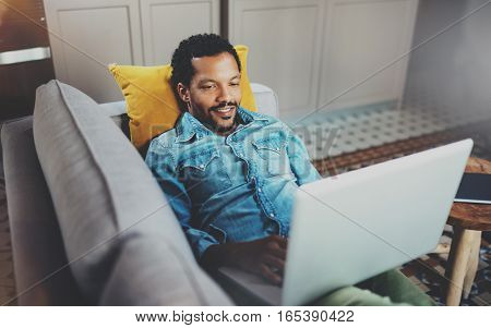 Happy young bearded African man spending rest time in sofa and looking at tablet modern home.Concept of people enjoying mobile devices.Blurred background