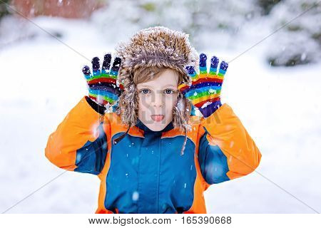 Funny little school kid boy in colorful clothes playing outdoors during snowfall. Active leisure with children in winter on cold snowy days. Happy child having fun and playing with snow