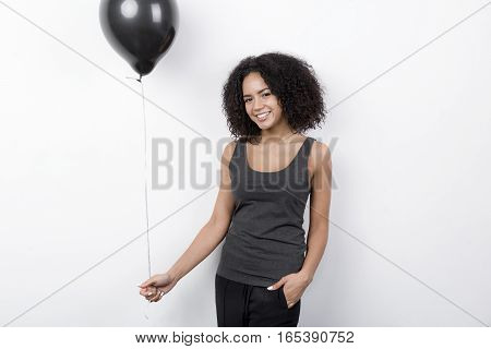 Happy woman indoors, holding black balloon in hand