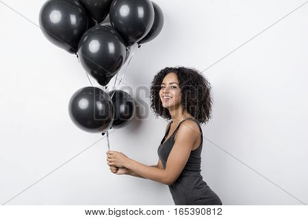 Beautiful woman wearing t-shirt and holding a bunch of black balloons, side view