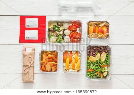 Healthy restaurant food. Chef prepared diet daily meals delivery. Fitness nutrition, vegetables, meat and fruits in foil boxes, cutlery, water and package. Top view, flat lay on wood with copy space