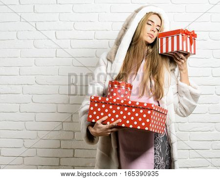 young fashionable sexy pretty woman or girl with long beautiful blonde hair in coat of white fur with hood and fashion makeup holding red big presents or gifts on brick wall studio background