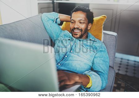 Smiling bearded African man spending free time in sofa and using digital tablet at modern home.Concept of young people enjoying mobile devices.Blurred background