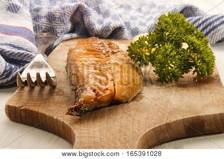 smoked mackerel from scotland with parsley and fork on a wooden board