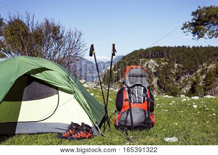 Camping with a backpack and a tent in the mountains on a sunny day.