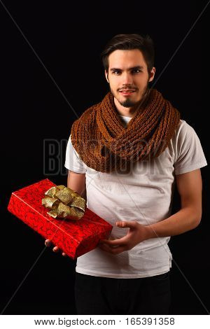 handsome bearded man in white shirt and orange knitted scarf with smiling face holding red present or gift on black studio background copy space