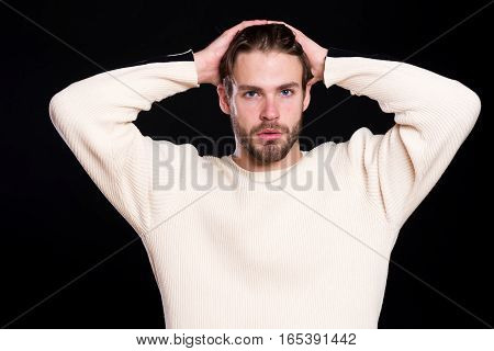 handsome bearded man or guy with beard on face in white sweater with raised hands on black background